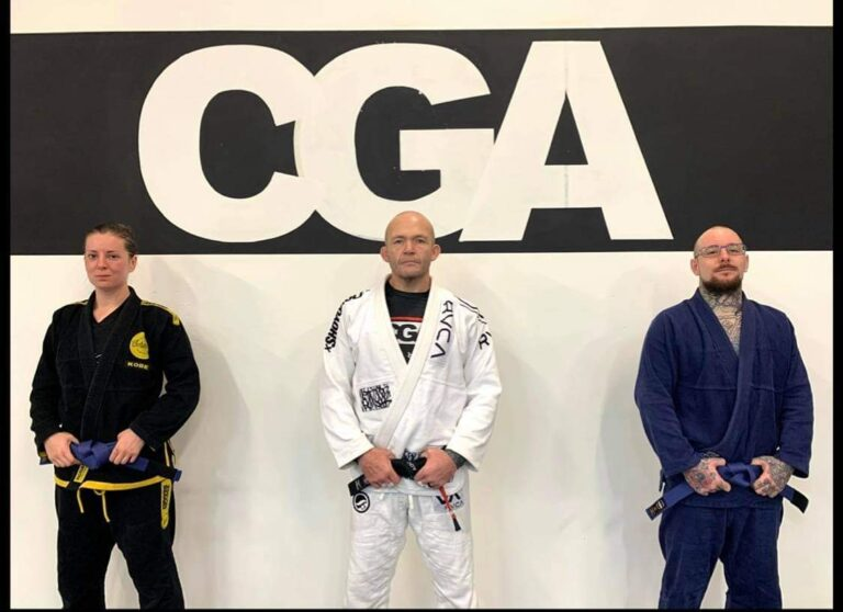 Becky was promoted to blue belt in December 2020 by Head Coach Laurie Dodson (centre), alongside her partner Mark (right)
